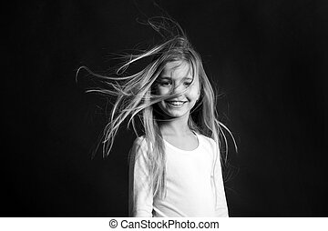 Beauty and hairdressing salon. Child model smiling with blowing long hair. Girl with adorable smile on dark background. Fashion, look, hairstyle. Happy childhood concept