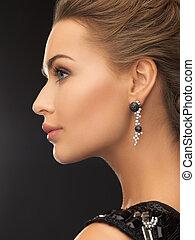 beauty and jewelery concept - woman wearing shiny diamond earrings