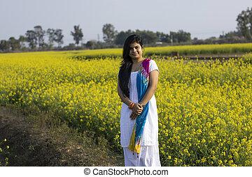 a beautiful woman in white dress standing near yellow mustard flower field