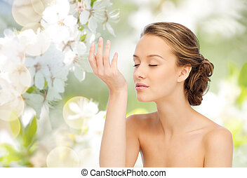 woman smelling perfume from wrist of her hand - beauty, ...