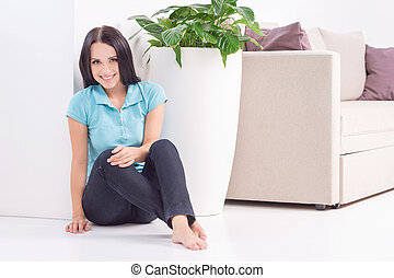 Beauty at home. Beautiful young woman sitting on the floor at home