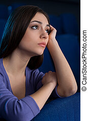 Beauty at the cinema. Attractive young woman holding head in hand while watching movie at the cinema