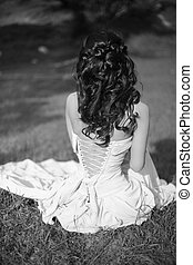 beauty black and white portrait. Brunette bride resting and sitting on green grass at spring park.