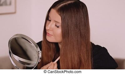 Beauty blogger applying makeup in front of mirror, portrait of beautiful model woman, skincare and cosmetic ad