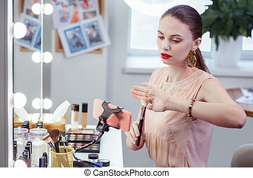 Nice pretty woman giving advice about makeup brush