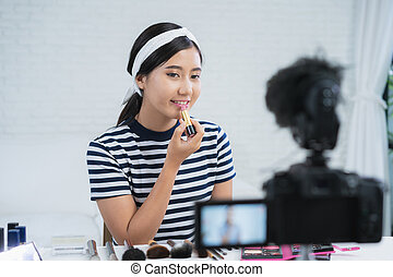 Beauty blogger present beauty cosmetics while sitting in front camera for recording video. Beautiful woman use lipstick while review make up tutorial broadcast live video to social network by internet.