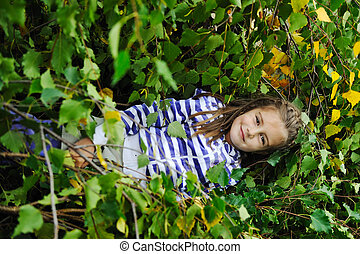 Beauty blond girl laying down on leaves ground