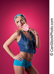 beauty blond girl lick candy on pink background