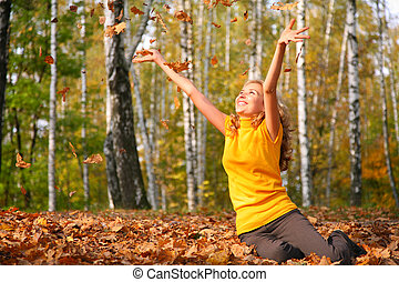 Beauty blond girl throws leaves in the park in autumn