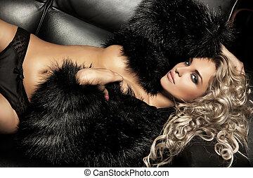 Beauty blond woman posing on black sofa
