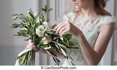 Beauty bride in bridal gown with bouquet and lace veil...