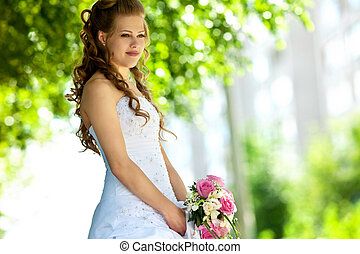 Beauty bride with flowers in sunny summer day