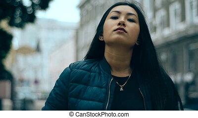 beauty brunette asian girl with purple lips posing in the street