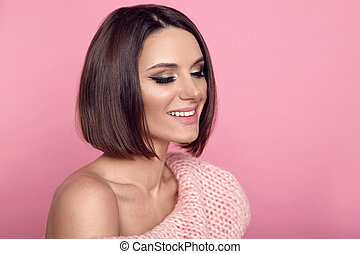 Beauty brunette makeup. Short bob hairstyle. Fashion girl model portrait. Attractive woman with smile and hair style posing over studio pink background.