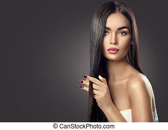 Beauty brunette model girl touching brown long healthy hair