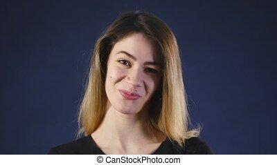 Beauty brunette smiling on dark background.