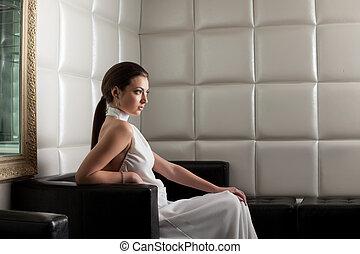 Beauty brunette woman on sofa in nightclub