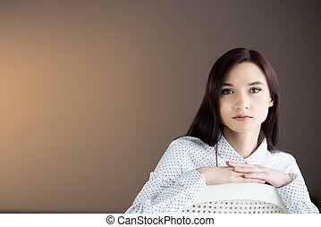 Beauty brunette woman sitting on the chair.