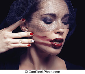 beauty brunette woman under black veil with red manicure...