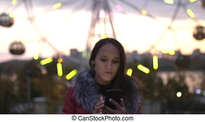 Beauty brunette young woman using mobile phone during walk on streets of night town with beautiful lights bokeh, slow motion. 3840x2160