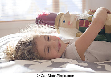 Beauty child who holding a nutcracker in bed