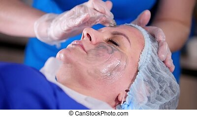 Beauty clinic. Young woman gets professional facial massage...