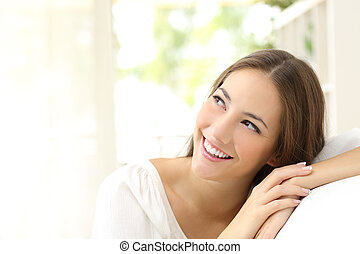 Beauty confident woman looking sideways sitting on a couch...