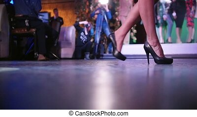 Beauty contest. Woman on high heels walking. Only legs shown