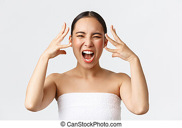 Beauty, cosmetology and spa salon concept. Close-up of outraged, mad distressed asian woman in bath towel screaming and shaking hands near head, feeling furious after bad service in beauty clinic