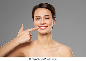 smiling young woman pointing to her mouth