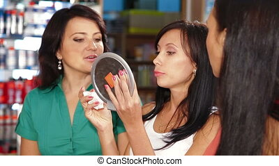 Beauty Department - Female Friends Testing Lipstick in...