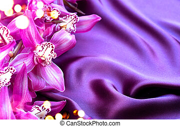 Beauty elegant violet silk and orchid flowers background