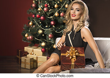 Beauty elegant woman with christmas present box in front of christmas tree