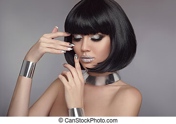 Beauty eye shadow Makeup, Silver Manicured polish nails. Bob hairstyle. Fashion Style Brunette Woman Portrait with black Short Hair and glitter lips isolated on gray background. Jewelry set.