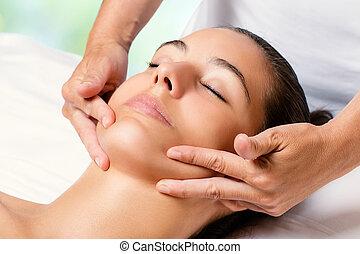 Beauty facial massage on female chin.