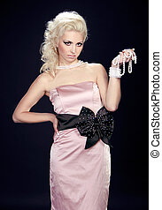 Beauty fashion blond woman model in pink dress on black background