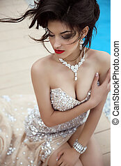 Elegant lady in luxurious glamour dress with oriental gemstones and expensive jewelry