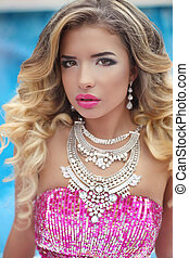 Beauty fashion girl model portrait. Blond woman with makeup, long wavy hair and luxury jewelry. Attractive female by outdoor swimming pool.