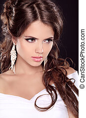 Beauty fashion girl model. Stare. Allure brunette woman with rich earrings isolated on black background