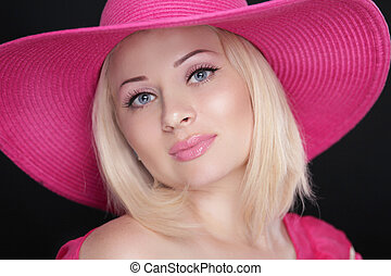 Beauty fashion girl portrait. Blond female in pink hat isolated on black background.