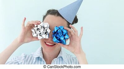 Girl holding silver bows against her eyes