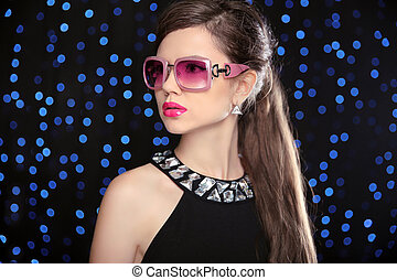 Beauty fashion model girl in sunglasses with bright makeup, long hair. Glamour woman isolated on blue holiday lights background.