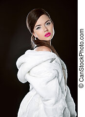 Beauty Fashion Model Girl in white mink Fur Coat. Beautiful Luxury Winter Woman isolated on black studio background
