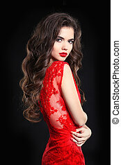 Beauty Fashion Portrait. Beautiful brunette Woman with Curly Hairstyle and makeup, wearing in red lace dress. elegant girl posing isolated on black studio background.