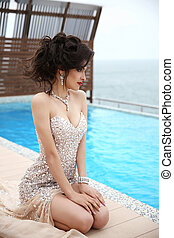 Beauty fashion sexy brunette elegant model woman in beaded dress with diamond jewelry, makeup red lips, hairstyle. Girl model posing by swimming pool, Resort.