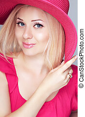Beauty fashion smiling blond woman in pink hat with makeup.