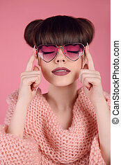 Beauty Fashion teen girl model in heart sunglasses. Portrait of Brunette with matte lips makeup and hairstyle posing over studio pink background.