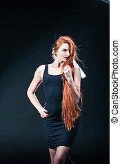Beauty ginger Girl Portrait. Healthy Long Red Hair. Beautiful Young Woman on black