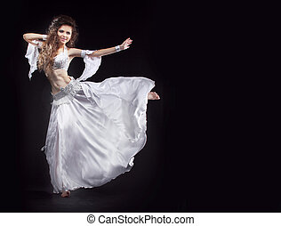 Beauty Girl belly dancer in white suit oriental dance in motion isolated on black background