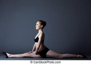 Beauty girl in black gymnast costume sit on split